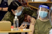 A Philippine military medical professional receives her first dose of Sinovac vaccine in Manila on Monday [Lisa Marie David/Reuters]