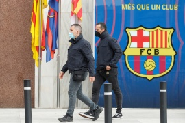 Mossos d'Esquadra police officers walk past the offices of FC Barcelona in Barcelona, Spain, March 1, 2021 [Albert Gea/Reuters]