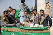 Armed Houthi followers ride on the back of a truck after participating in a funeral of Houthi fighters killed in recent fighting against government forces in Yemen's oil-rich province of Marib, on February 20, 2021 [File: Khaled Abdullah/Reuters]