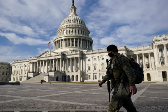 A National Guardsman passes the US Capitol on February 26, 2021, about a month after the Capitol riot [File: Kevin Lamarque/Reuters]