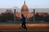 A person jogs outside the security perimeter fence surrounding the US Capitol on March 4, 2021 [Jim Urquhart/Reuters]