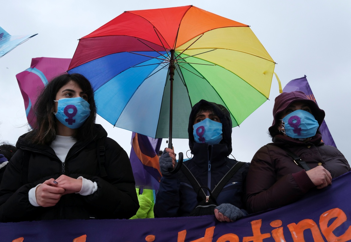 Demonstrators wearing face masks to prevent the spread of the coronavirus hold a rainbow-coloured umbrella during a rally before the International Women's Day in Istanbul, Turkey. [Murad Sezer/Reuters]