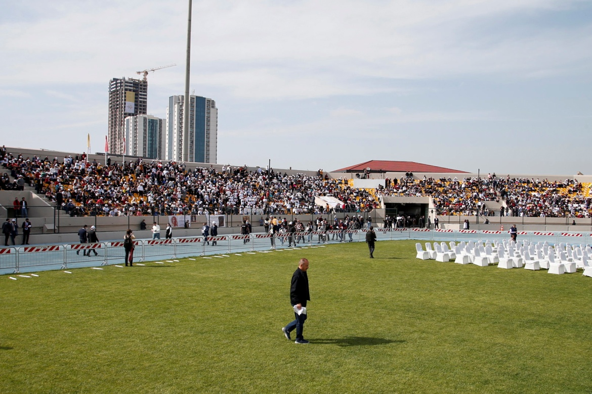 People wait for the start of a mass led by Pope Francis at the Franso Hariri Stadium in Erbil. [Azad Lashkari/Reuters]