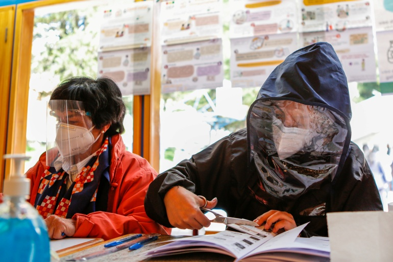 People wear face masks and face coverings while they work at a polling station during regional elections in La Paz, Bolivia, on March 7, 2021 [Manuel Claure/Reuters]