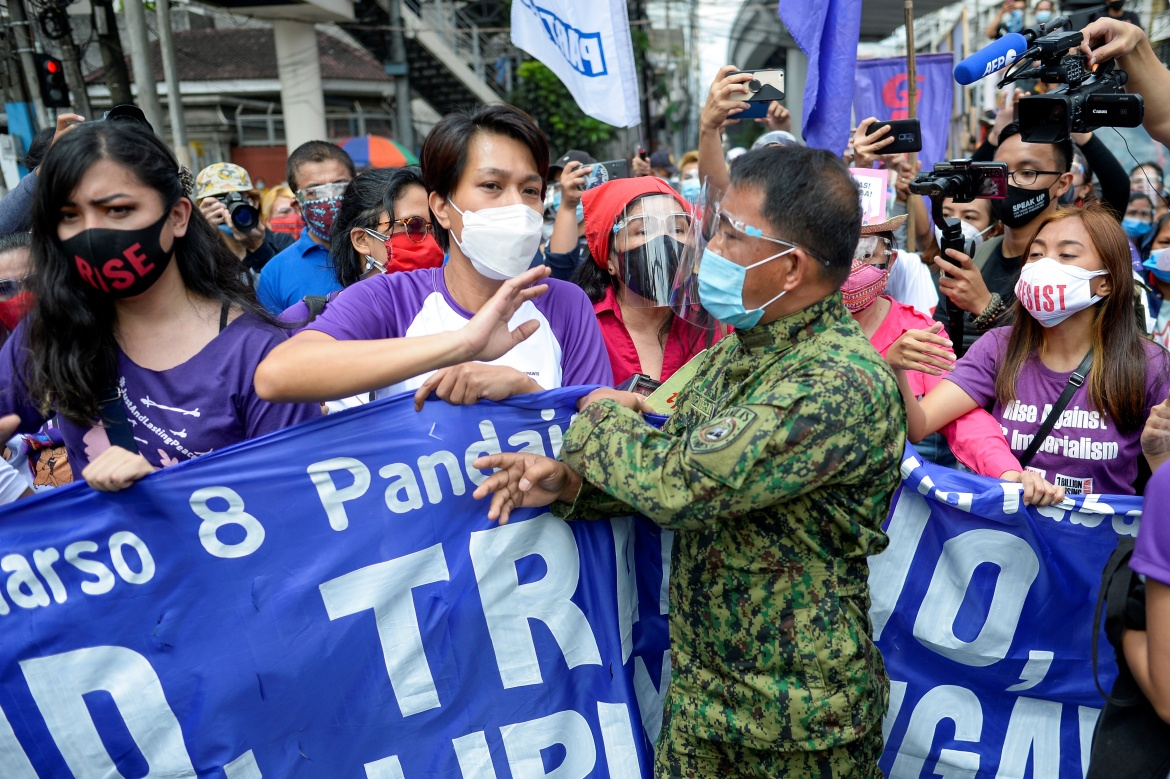 A police officer blocks demonstrators holding a banner as they protest during the International Women's Day, in Manila, Philippines. [Lisa Marie David/Reuters]