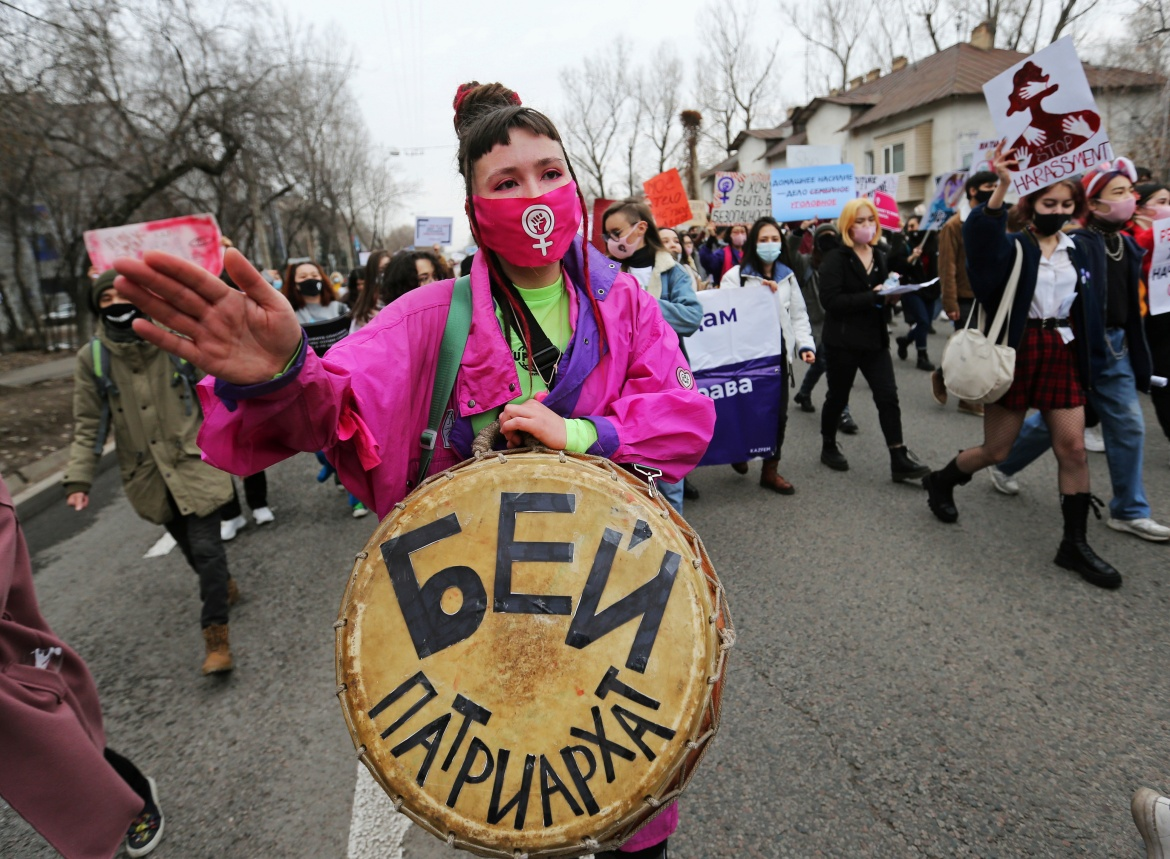 A woman beats a drum with a sign that translates as 'Beat patriarchy' as she takes part in a march to mark International Women's Day in Almaty, Kazakhstan. [Pavel Mikheyev/Reuters]