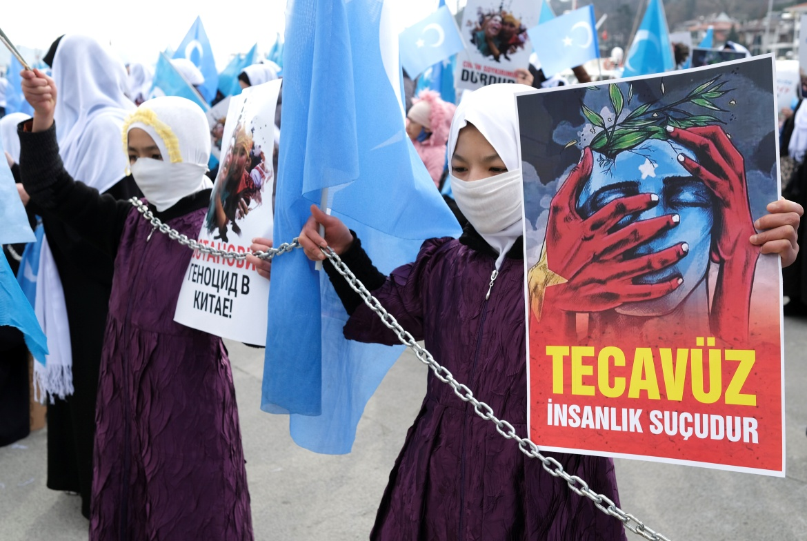 An Ethnic Uighur demonstrator holding a placard that reads 'Rape is crime of humanity' takes part in a gathering on the occasion of International Women's Day in Istanbul, Turkey, to protest against China's treatment of Uighurs. [Murad Sezer/Reuters]