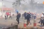 In the central city of Loikaw in Kayah State, demonstrators flee away from tear gas during an anti-coup protest on Tuesday [Mizzima Burmese/Reuters]