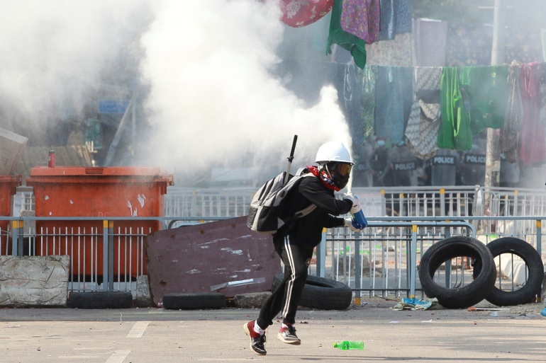 An anti-coup demonstrator sprays a fire extinguisher for cover as he runs away from security forces in Yangon on Tuesday [Reuters]