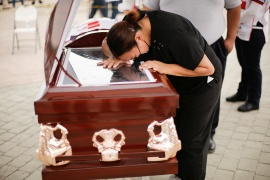 A woman crying over the coffin of Josue Correa, a former paramedic who died of COVID-19 in Ciudad Juarez, Mexico [File: Jose Luis Gonzalez/Reuters]