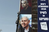 "Labourers hang a Likud party election campaign banner depicting party leader Israeli Prime Minister Benjamin Netanyahu and his challenger Yesh Atid party leader Yair Lapid, ahead of a March 23 ballot, in Jerusalem March 10, 2021. The writing in Hebrew reads: 'Next Prime Minister: Lapid or Netanyahu"". [Ammar Awad/Reuters]"