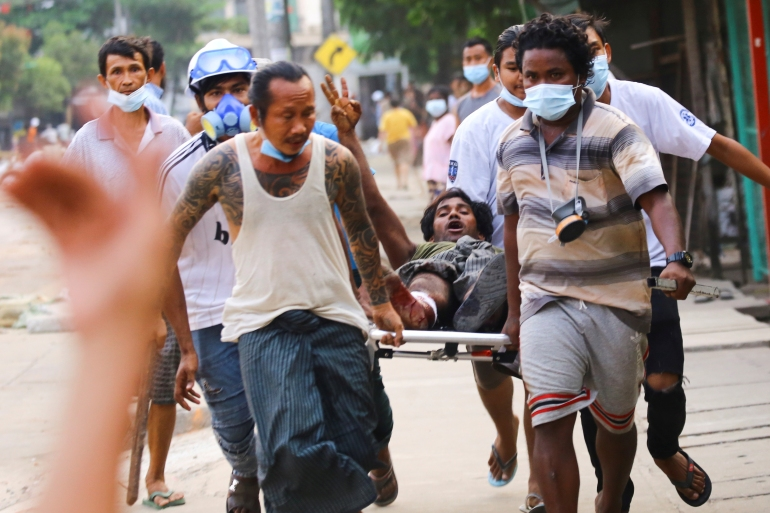 People carry a protesters who was shot during the security force crackdown on anti-coup protesters in Thingangyun, Yangon. [Reuters]
