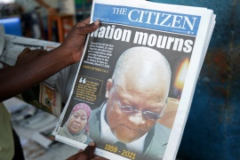 A man holds a newspapers following the death of Tanzania's President John Magufuli [Emmanuel Herman/Reuters]