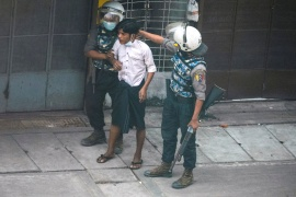 Riot police officers detain a demonstrator in Yangon during a protest against the military coup [Stringer/Reuters]