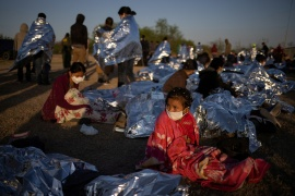Hennessy, 4, from Honduras, awakes at sunrise next to others who took refuge near a baseball field after crossing the Rio Grande river into the United States from Mexico on rafts, in La Joya, Texas, US, March 19, 2021 [File: Adrees Latif/Reuters]