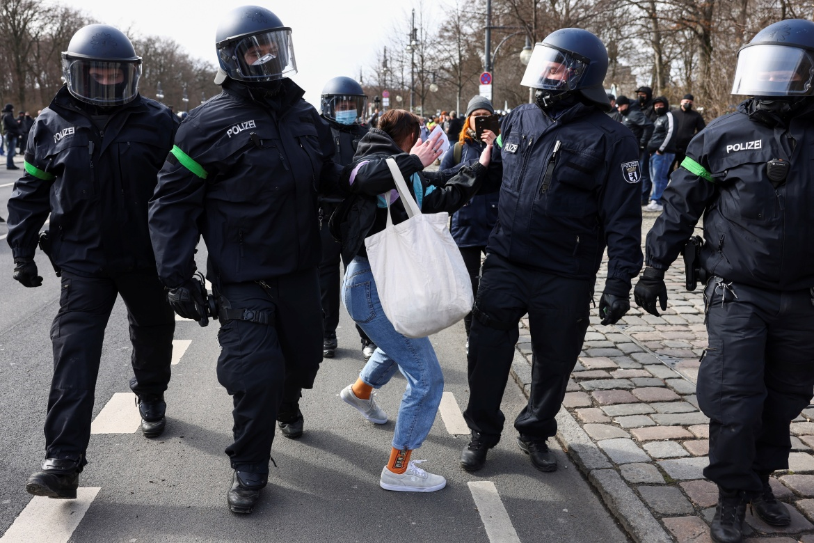 Police officers detain a demonstrator during a rally against the government's restrictions following a rise in COVID cases in Berlin. [Christian Mang/Reuters]