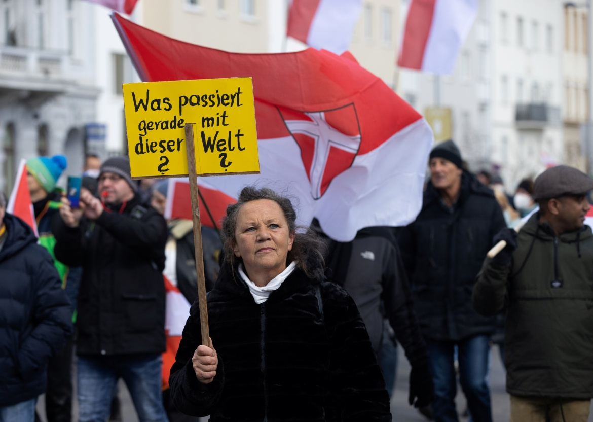 A woman holds a sign as she takes part in a demonstration against the coronavirus measures in Vienna, Austria. [Lisi Niesner/Reuters]