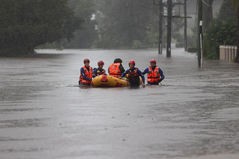 Uma equipe de resgate do Serviço de Emergência Estadual usa uma jangada inflável para levar um residente à segurança em Sydney.  [Loren Elliott / Reuters]