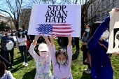Sisters Kelly, 9, and Chole, 8, hold a sign at a rally to protest recent violence against people of Asian descent at McPherson Square near the White House in Washington, U.S. March 21, 2021. REUTERS/Erin Scott (Getty Images)