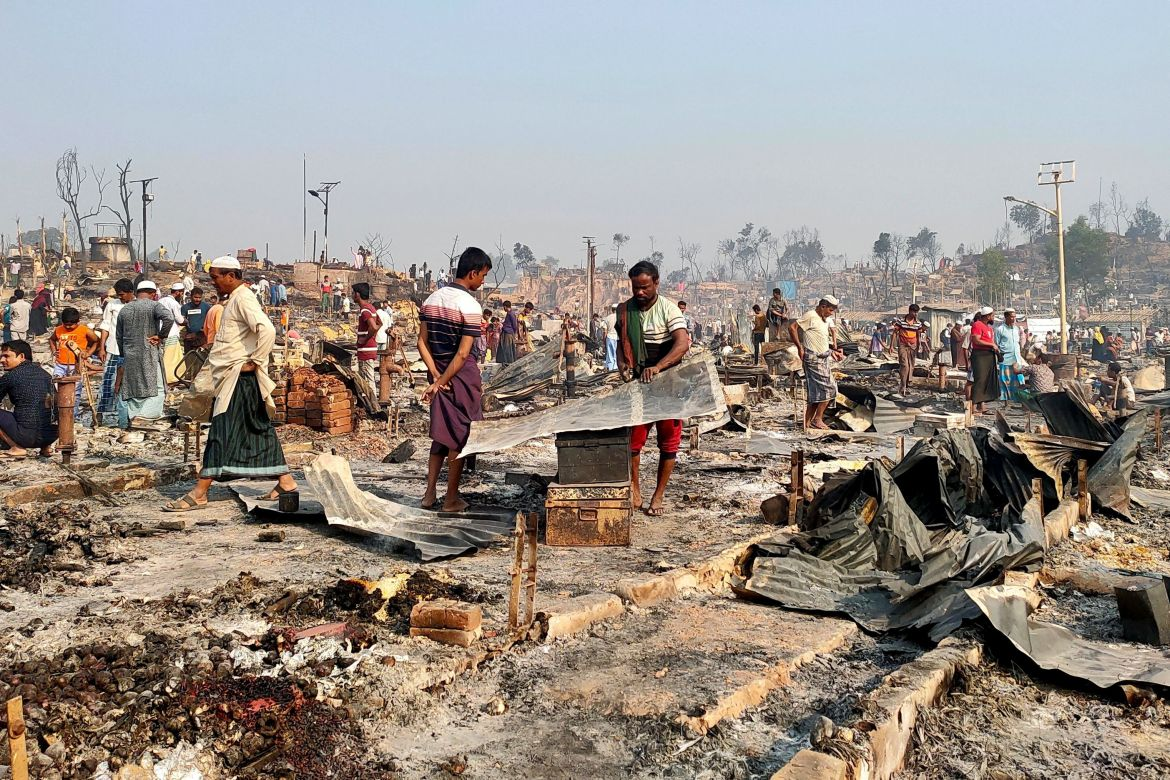Rohingya refugees sift through rubble at the site where their shelter has been burned down. [Ro Yassin Abdumonab/Reuters]