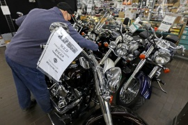 Gary Haines of Cycle World Superstore places SOLD signs on Harley-Davidson motorcycles that have been purchased by customers in Canada, where sales of pleasure vehicles are surging [File: Chris Helgren/Reuters]
