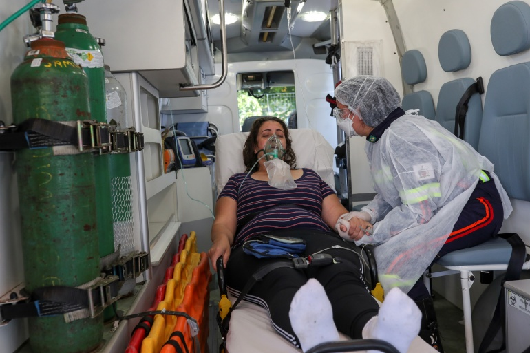 Nurse Danila Bassi holds the hand of Marley das Gracas, 42, who tested positive for COVID-19, inside an ambulance, in Sao Bernardo do Campo, Brazil, on March 24 [Amanda Perobelli/Reuters]