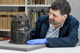 Neil Curtis, head of museums and special collections, is seen with a Benin Bronze depicting the Oba of Benin at the University of Aberdeen in Scotland [University of Aberdeen/Handout via Reuters]