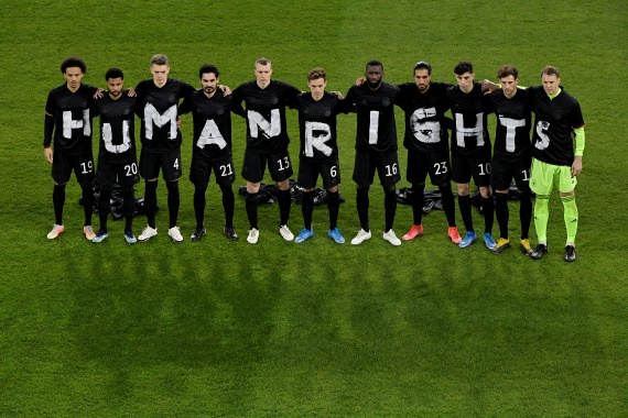 German players staging their protest ahead of kickoff in the World Cup qualifier [Tobias Schwarz/Reuters]
