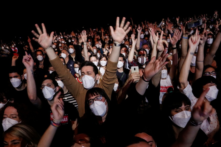 People wearing protective masks attend a concert of 'Love of Lesbian' at the Palau Sant Jordi, the first massive concert since the beginning of the coronavirus pandemic in Barcelona, Spain, March 27, 2021 [Albert Gea/ Reuters]