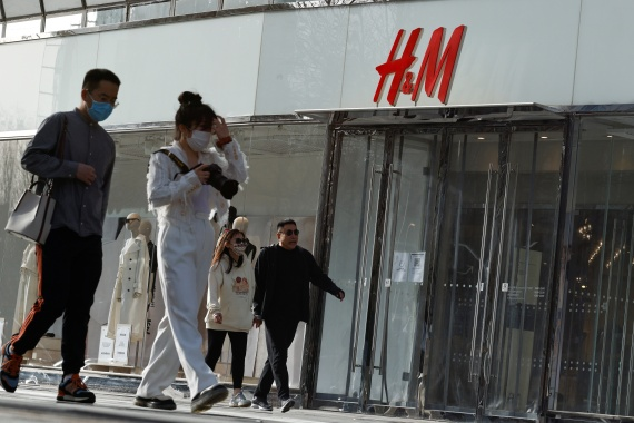 People walk past an H&M store in a shopping area in Beijing, China, March 28, 2021 [Thomas Peter/ Reuters]
