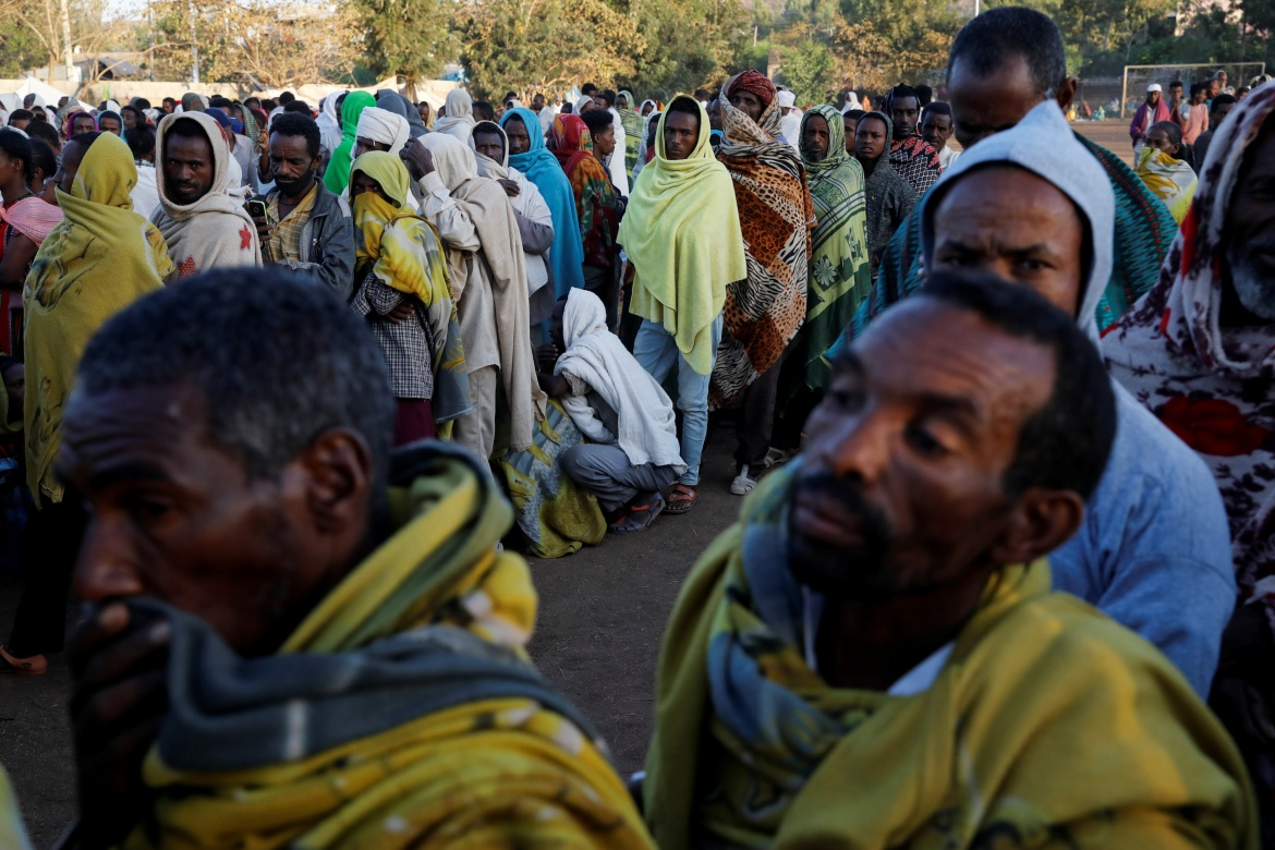 Displaced people queue for food at the Tsehaye primary school, which was turned into a temporary shelter for people displaced by conflict, in the town of Shire, Tigray region. [Baz Ratner/Reuters]