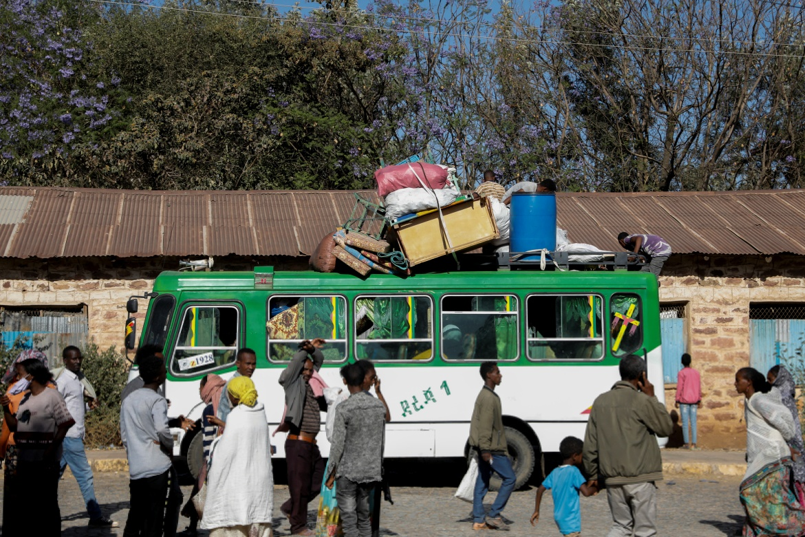 A bus carrying displaced people arrives at the Tsehaye primary school, sheltering people displaced by conflict, in Shire. [Baz Ratner/Reuters]