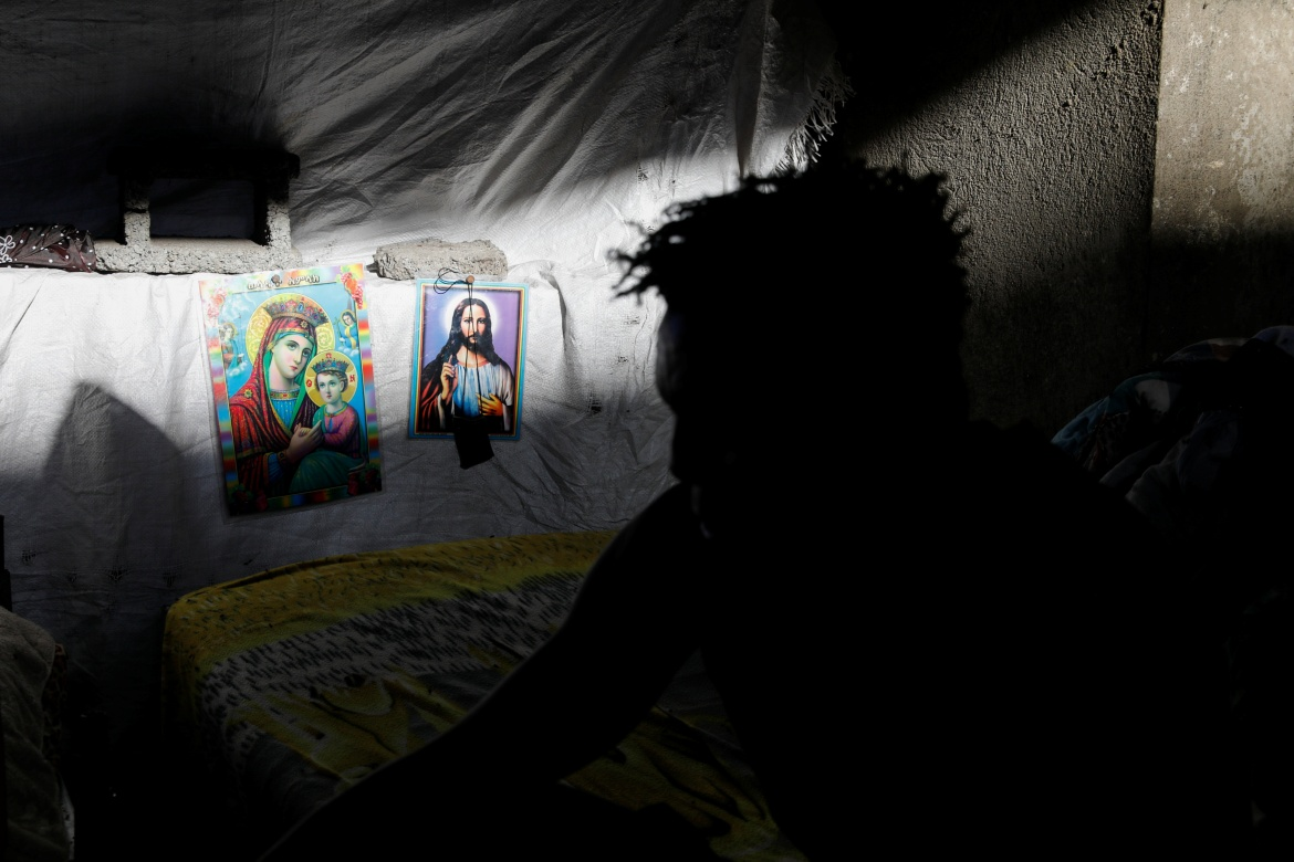 Religious posters hang next to the bed of a man in a building under construction at the Shire campus of Aksum University. [Baz Ratner/Reuters]