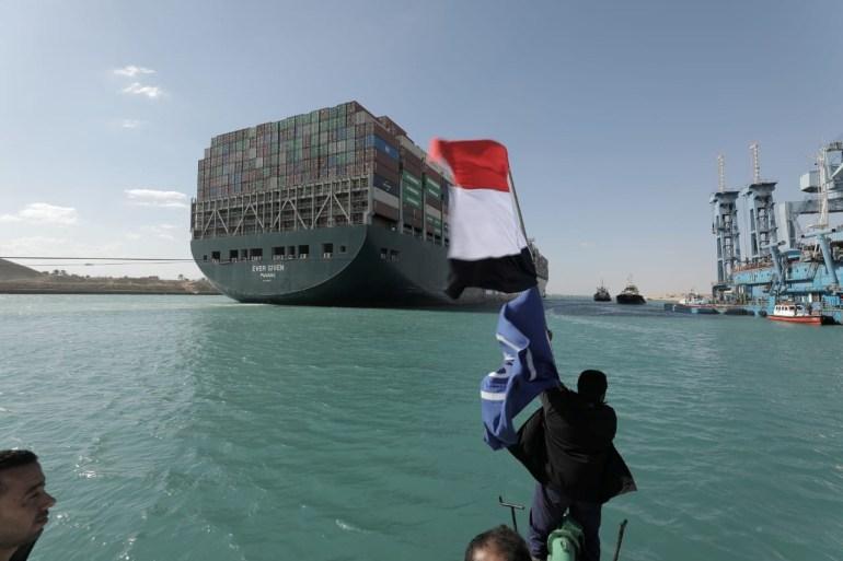 Seorang pria mengibarkan bendera Mesir saat Ever Given, salah satu kapal kontainer terbesar di dunia, terlihat setelah sepenuhnya dikibarkan di Terusan Suez Otoritas Terusan Suez via Reuters