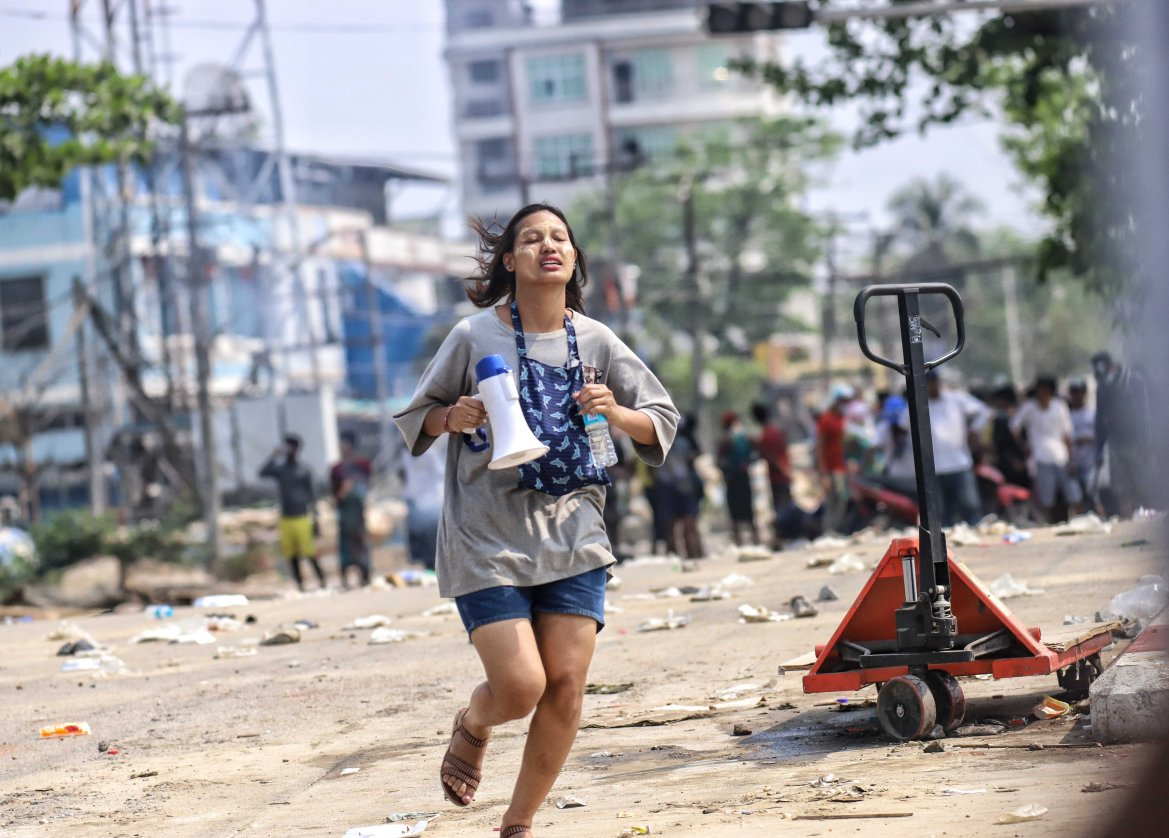 A woman carrying a megaphone runs during the protest in Hlaing Thayar Township, Yangon. [Anadolu]