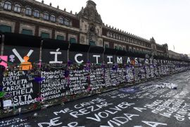 Names of femicide victims, slogans and flowers cover a barricade outside the National Palace ahead of International Women's Day demonstrations on March 8 [Bloomberg]