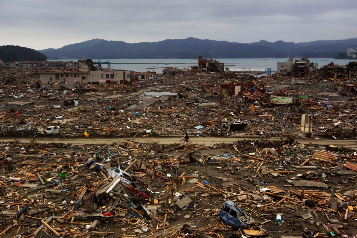 A survivor of the earthquake and tsunami rides his bicycle through the levelled city of Minamisanriku, in northeastern Japan, four days after the tsunami in this March 15, 2011, file photo. [David Guttenfelder/AP Photo]