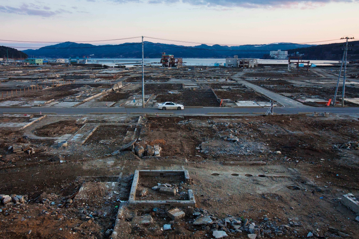 A car passes through the levelled city of Minamisanriku, Miyagi Prefecture, northeastern Japan, almost one year after the tsunami in this February 23, 2012, file photo. [David Guttenfelder/AP Photo]