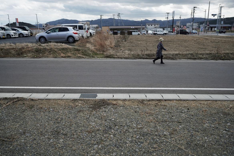 A woman walks through the city of Minamisanriku, Miyagi Prefecture, northern Japan, Saturday, March 6, 2021, nearly ten years after the Tsunami. [Eugene Hoshiko/AP Photo]