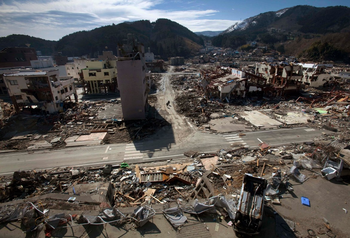 Residents of the tsunami and earthquake-destroyed town of Onagawa in Miyagi Prefecture, northern Japan, walk down an empty street in this March 19, 2011, photo. [David Guttenfelder/AP Photo]