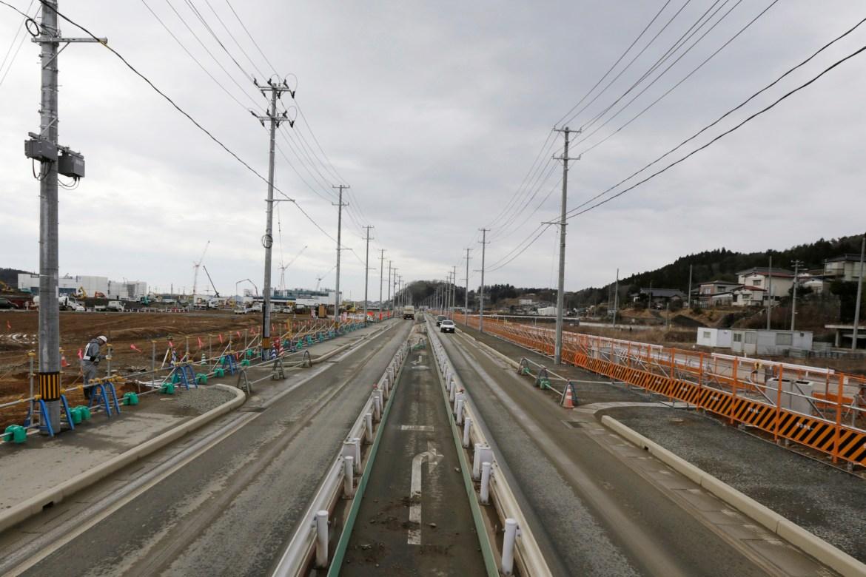 A worker checks the construction site in Kesennuma, Miyagi Prefecture, northeastern Japan in this March 7, 2016 photo. [Eugene Hoshiko/AP Photo]
