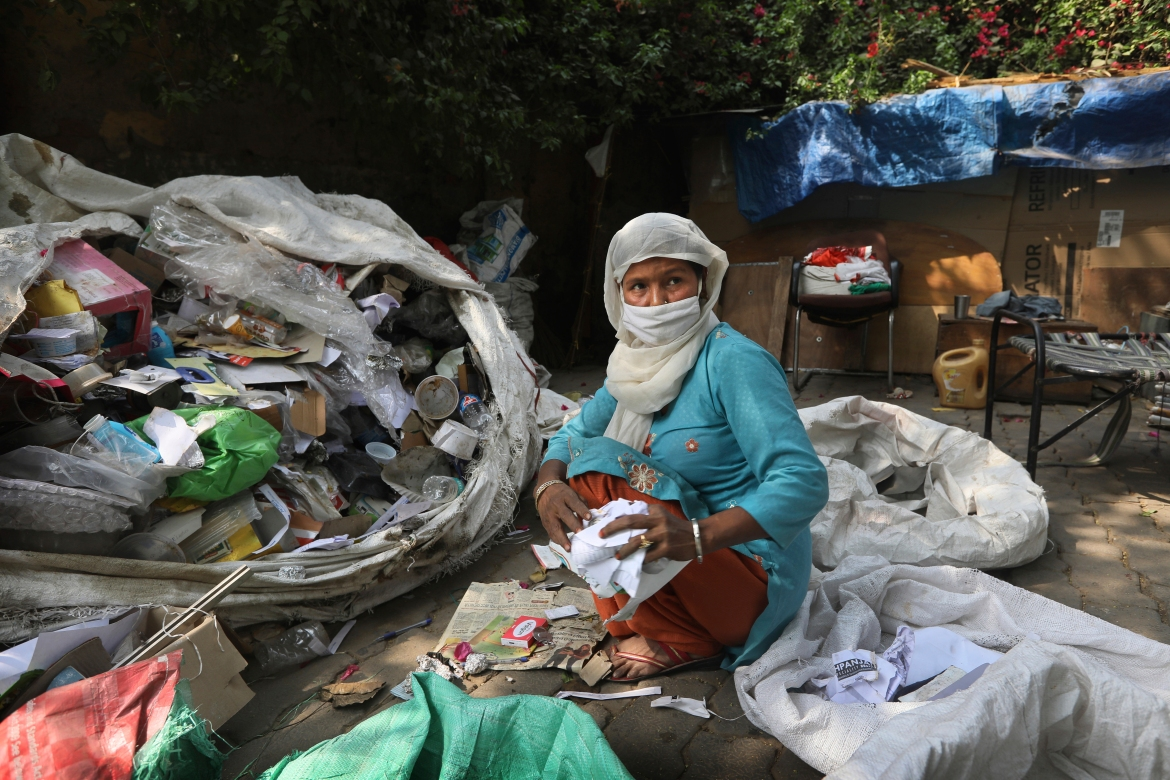 Manuwara Begun, 46, sorts out rubbish collected from households in New Delhi, India. Begun lives in a cardboard hut behind a five-star hotel in the heart of New Delhi and feels the inequity keenly. [Manish Swarup/AP Photo]
