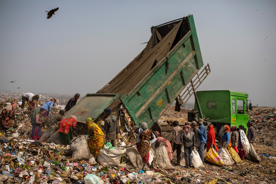 Workers surround a municipal garbage truck dumping rubbish at the Bhalswa landfill on the outskirts of New Delhi. [Altaf Qadri/AP Photo]