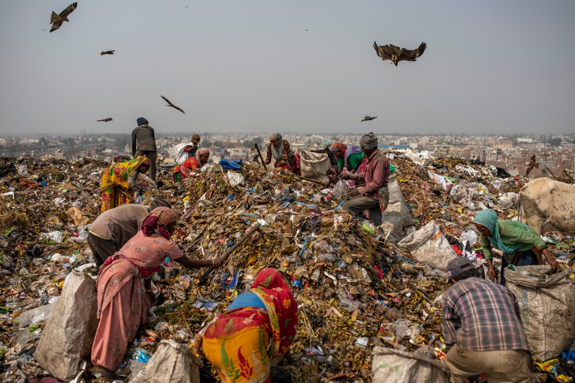 Rubbish collectors look for recyclable materials at Bhalswa landfill on the outskirts of New Delhi. [Altaf Qadri/AP Photo]