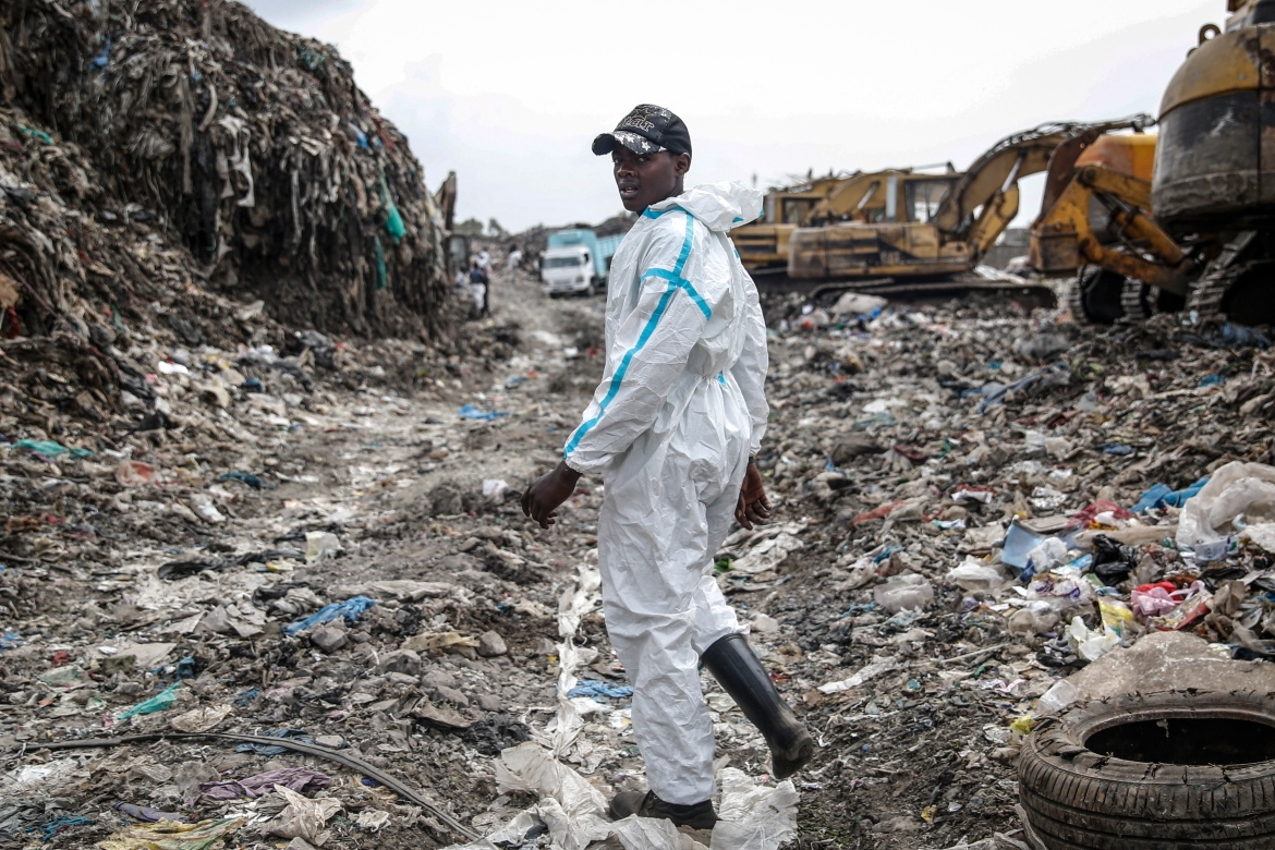 Isaac Kivai scavenges recyclable materials for a living at Dandora, the largest rubbish dump in the Kenyan capital of Nairobi, Sunday, March 28, 2021. He wears a protective medical suit he and his friends had found in the rubbish. The waste pickers say the gear protects them from the weather during the rainy season. (AP Photo/Brian Inganga)