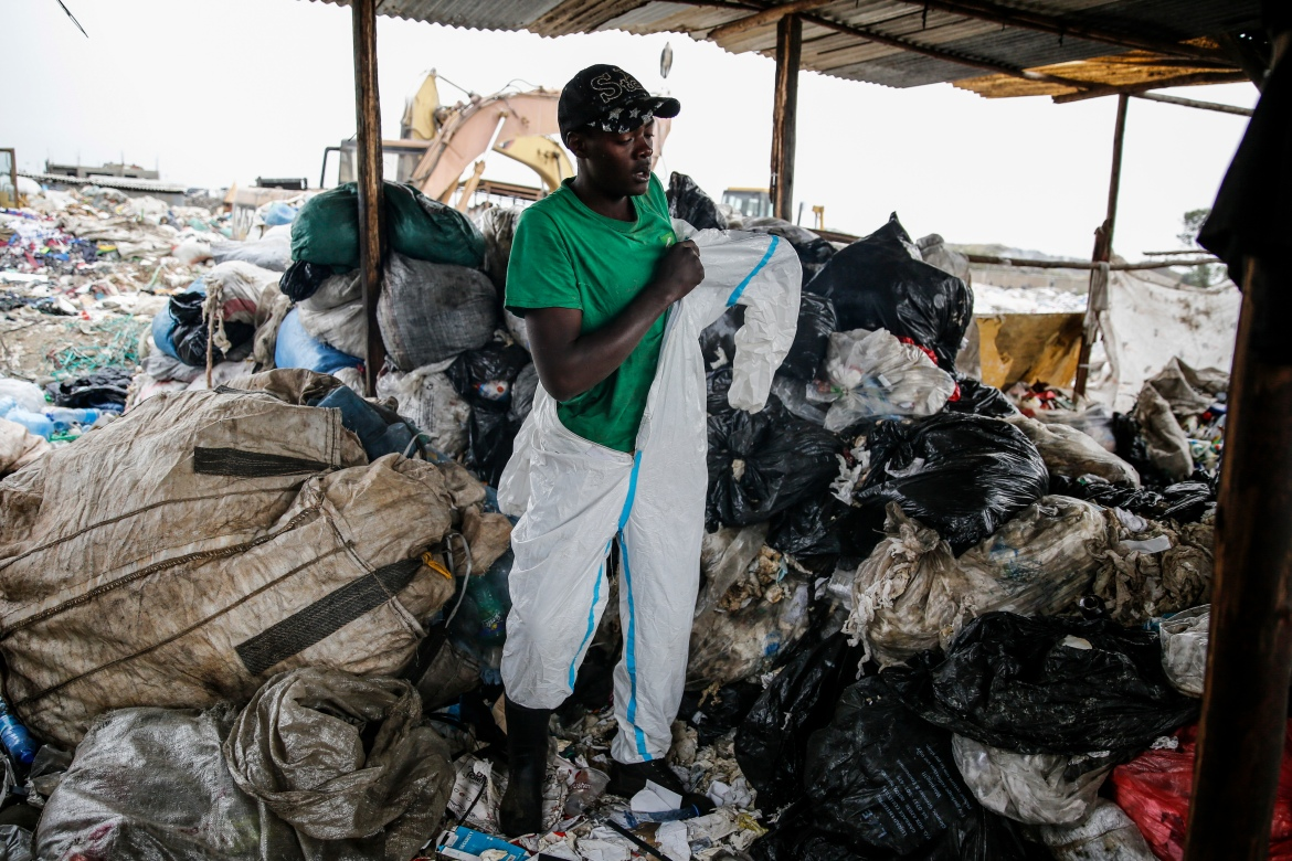 Isaac Kivai, who scavenges recyclables for a living, puts on a protective suit found in the rubbish at Dandora. [Brian Inganga/AP Photo]