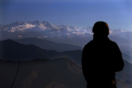 An Indian soldier looks towards the snow-covered Pir Panjal range in the Himalayas from a forward post at LoC between India and Pakistan, in Poonch, Indian-administered Kashmir [File: Channi Anand/AP]