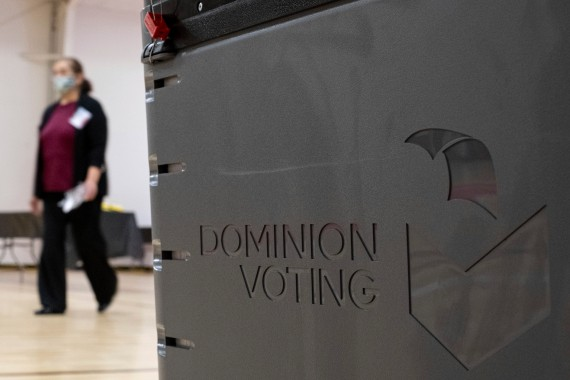 A worker passes a Dominion Voting ballot scanner while setting up a polling location at an elementary school in Gwinnett County, Georgia [File: Ben Gray/AP]