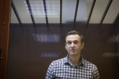 Russian opposition leader Alexey Navalny stands in a cage during a court hearing [File: Alexander Zemlianichenko/AP]