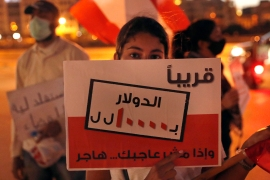 A protester holds an Arabic placard that reads: 'Soon the dollar = 10,000 Lebanese pounds and if you are not happy, immigrate' [Hussein Malla/AP]